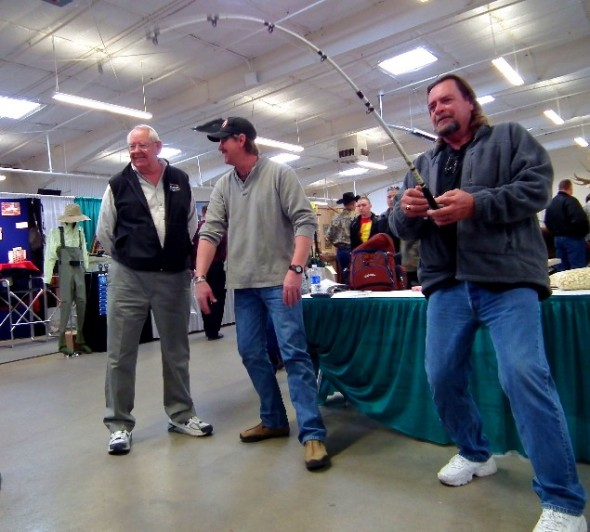 Bob Gerding watches as Mike Giddings enjoys reeling in a big one on a simulator machine featured at the a recent show.