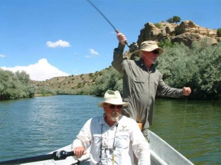 Larry Johnson mans the oars of his drift boat while Tim McCarthy casts during a recent trip down the lower San Juan River.