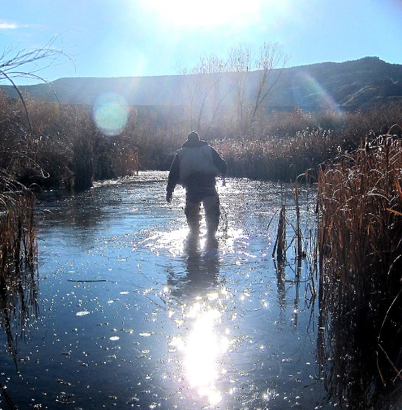 An angler hikes through a thin sheet of ice  while fishing the San Juan River.