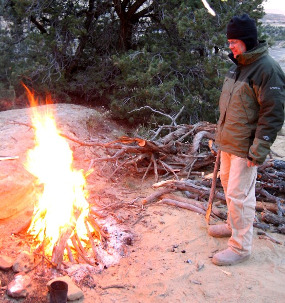 Man tends roaring camp fire.