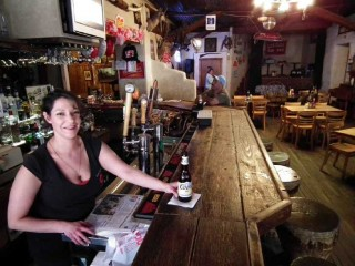 A pretty bartender at Los Ojos Bar in Jemez Springs serves up a cold Coors.