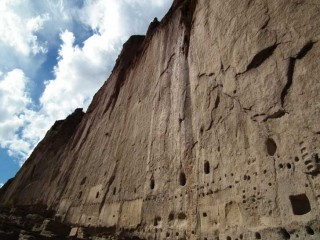 A sheer cliff face towers over the Long House area at Bandelier National Monument in New Mexico.