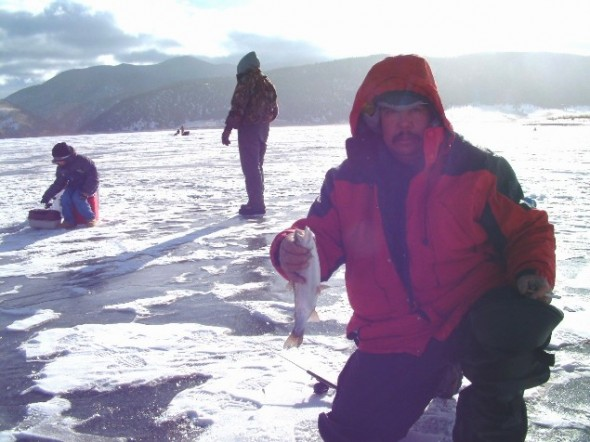 Man ice fishing in NM at Eagle Nest shows off trout