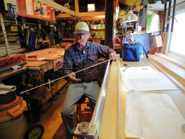 Bruce Smith inspects a piece of bamboo for a custom crafted fishing rod.