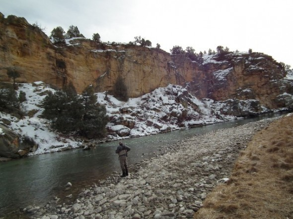 Snow dusted cliffs overlook stretches of the Rio Chama in northern New Mexico while an angler rigs up on the water below.