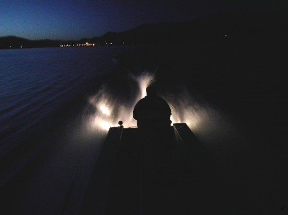 silhouette of a man  driving boat on lake at night