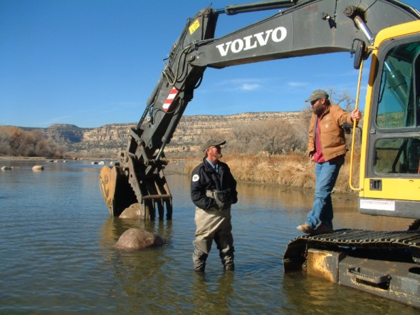 men talking by heavy equipment in san juan river