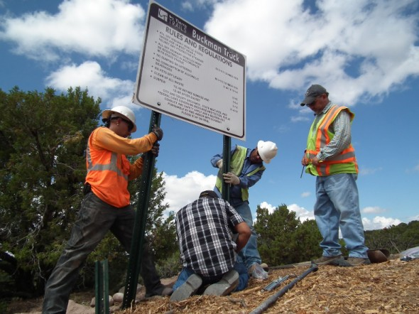 workers installing signs at motocross park