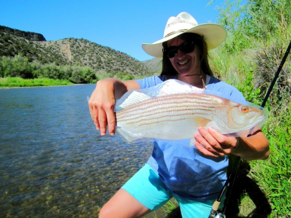 Kirtland Central High School Teacher, Sonnin Dahl, poses with one of plastic fish used in the Project Wild program to familiarize participants with the many aquatic species found in New Mexico.