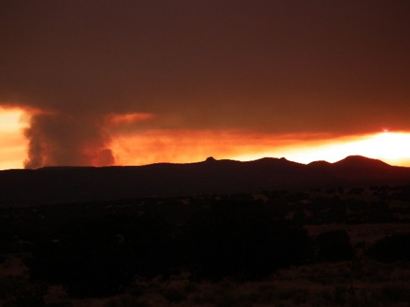 As smoke rises from the Las Conchas Fire the setting sun turns the sky a blazing red.