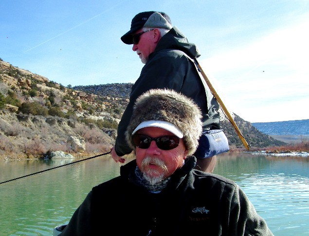 man in furry hat driving boat